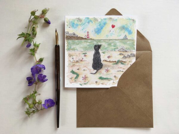 Blank greetings card. This a beautifully sentimental limited edition dog print by artist Amanda Reynolds. A gorgeous black Labrador sits solitary on a beach looking out to the horizon where a red heart balloon floats away into the distance. Titled Real Friends Hold Our Hearts Forever this painting is a gentle nod to mans best friend who has passed away and is a dog missed everyday. There is a castle and lighthouse in the distance and a small sailing boat on the sea. The beach is scattered with star fish and sea weeds and a rather large stick that the black dog has collected.
