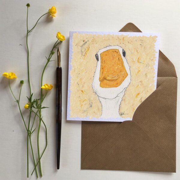 Funny Goose Greeting Card. This is a picture of a goose looking straight at you like it's taken a selfie and it is white with a yellowy orange beak and it is surrounded by a crème background with streaks of yellows, browns, greys and blacks.
